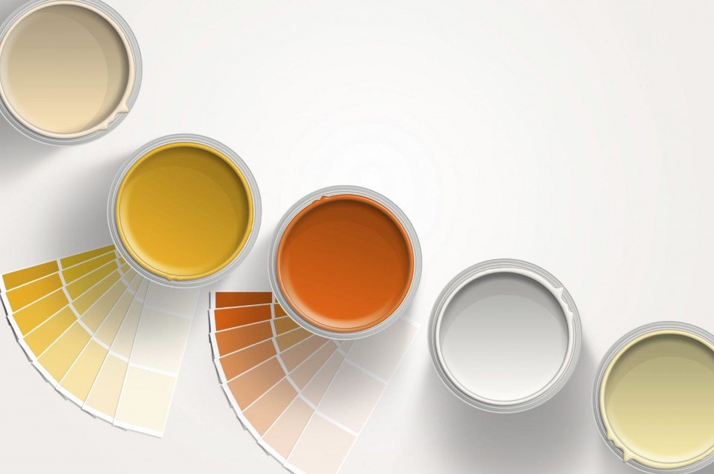 Five paint cans - yellow, orange, white on white background